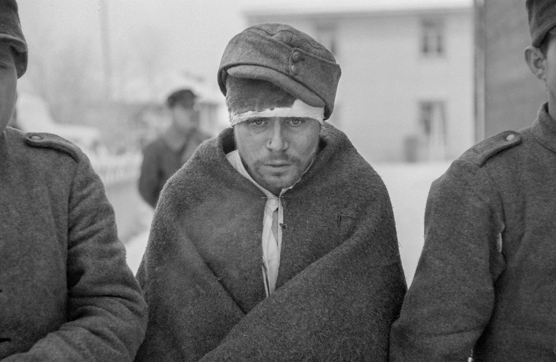 Tre sovjetiska krigsfångar. En av dem har ett blodigt bandage runt huvudet och är insvept i en filt.