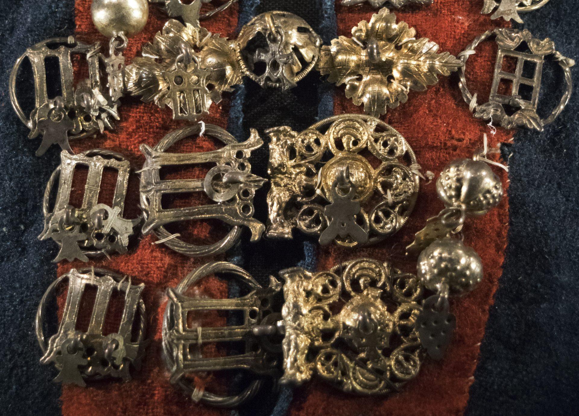 Foto som visar detaljbild av en silverkrage med hängen och spännen