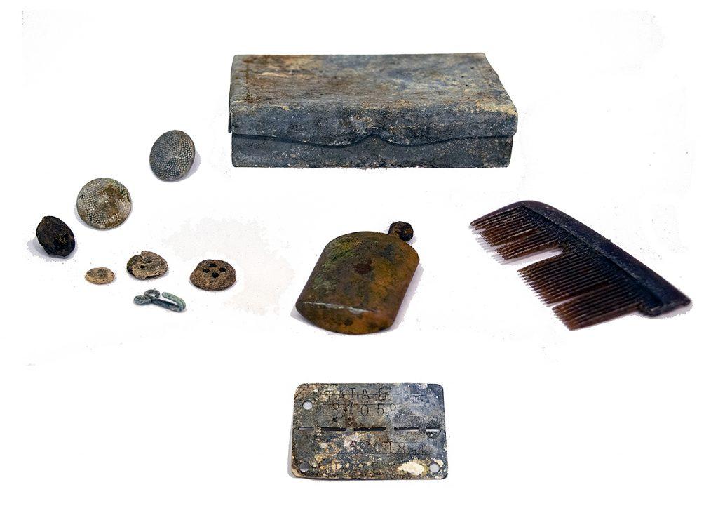 Ett plåtask, en kam, en cigarettändare, några knappar och en id-bricka som har tillhört krigsfången.