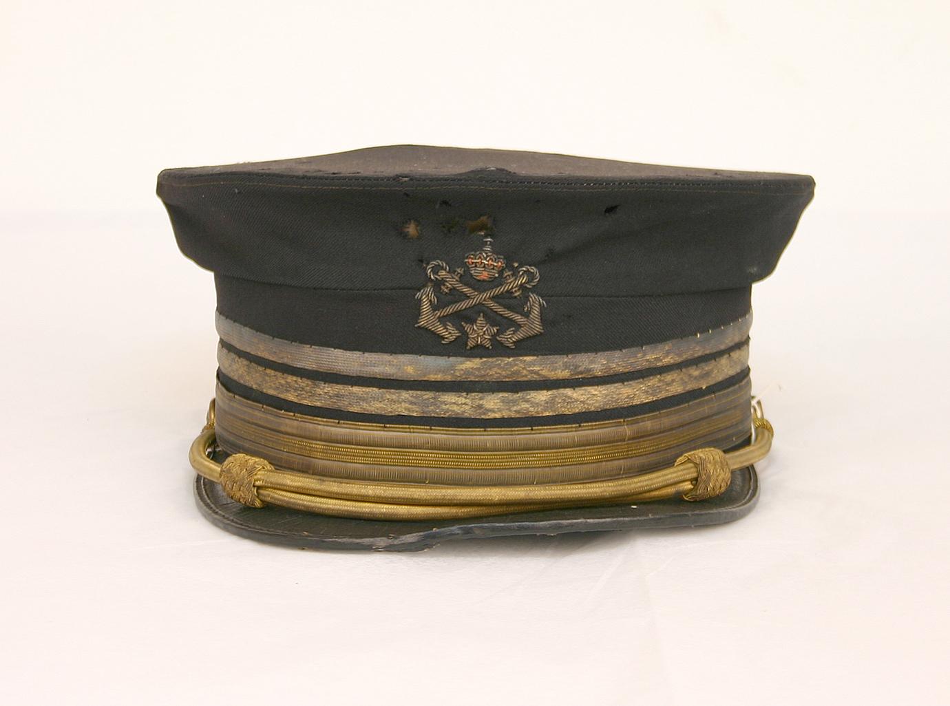 En svart skärmmössa med guldränder och ett märke med två korslagda ankare, en krona och en stjärna.
