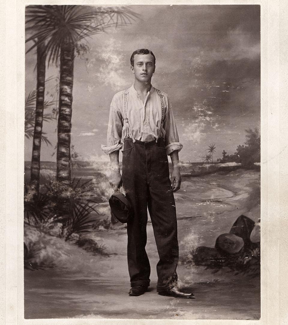En ung man i mörka byxor och ljus skjorta står i en studio med målade palmträd som bakgrund.