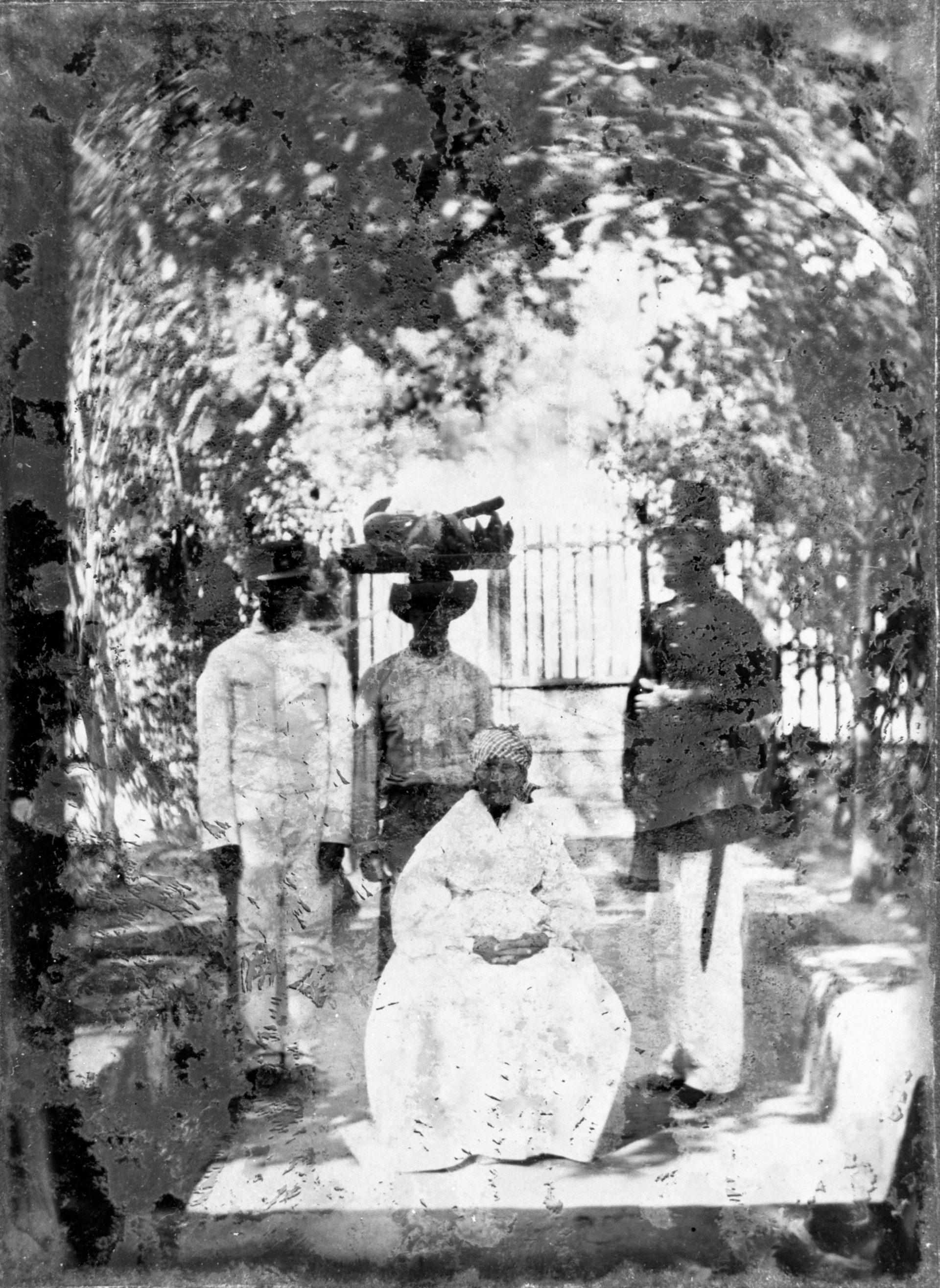 Foto av en gammal kvinna sittandes framför tre yngre män, varav en i uniform.
