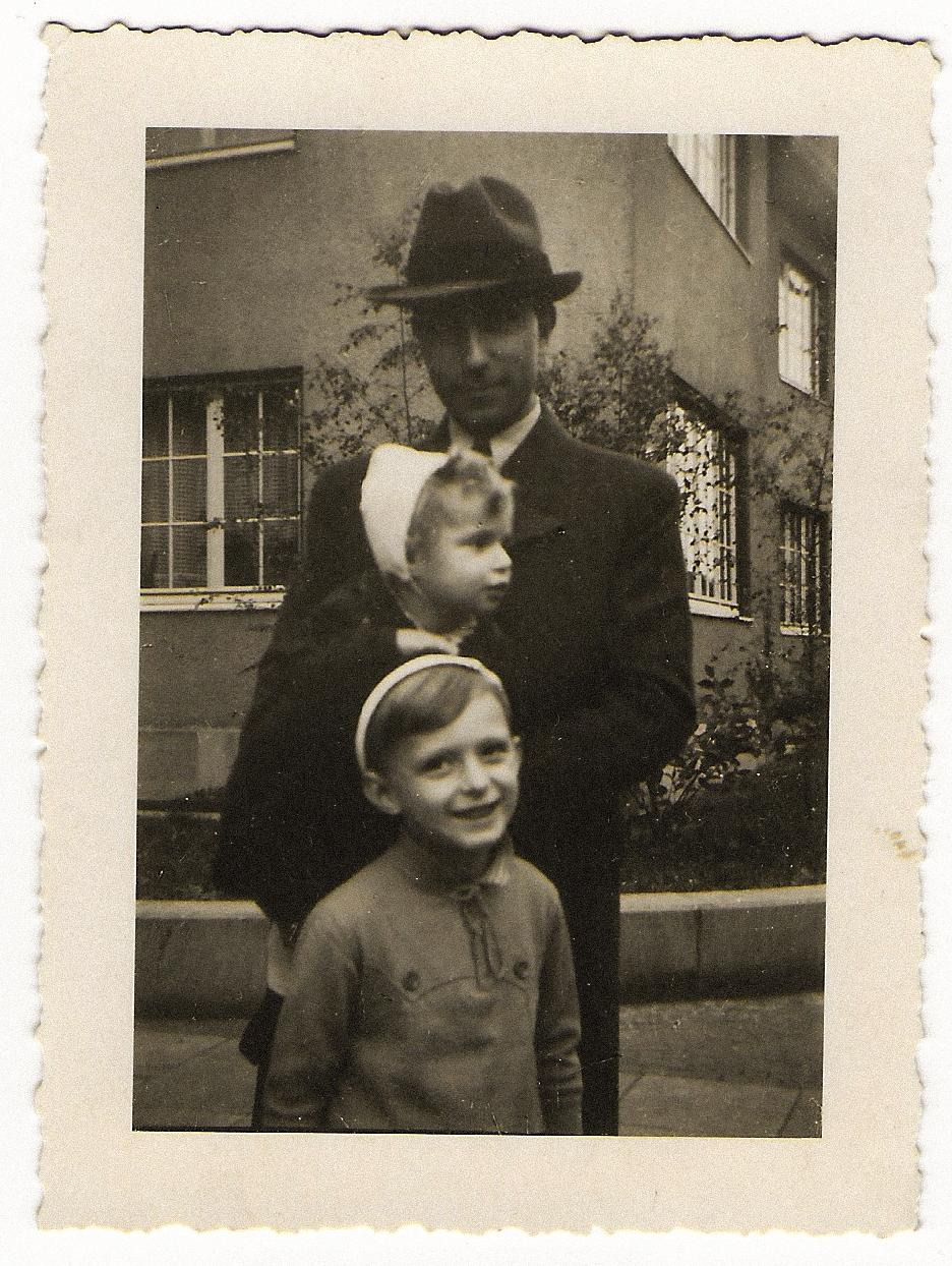 En man i hatt och kostym håller i ett litet barn. Framför står en pojke som ler mot kameran.
