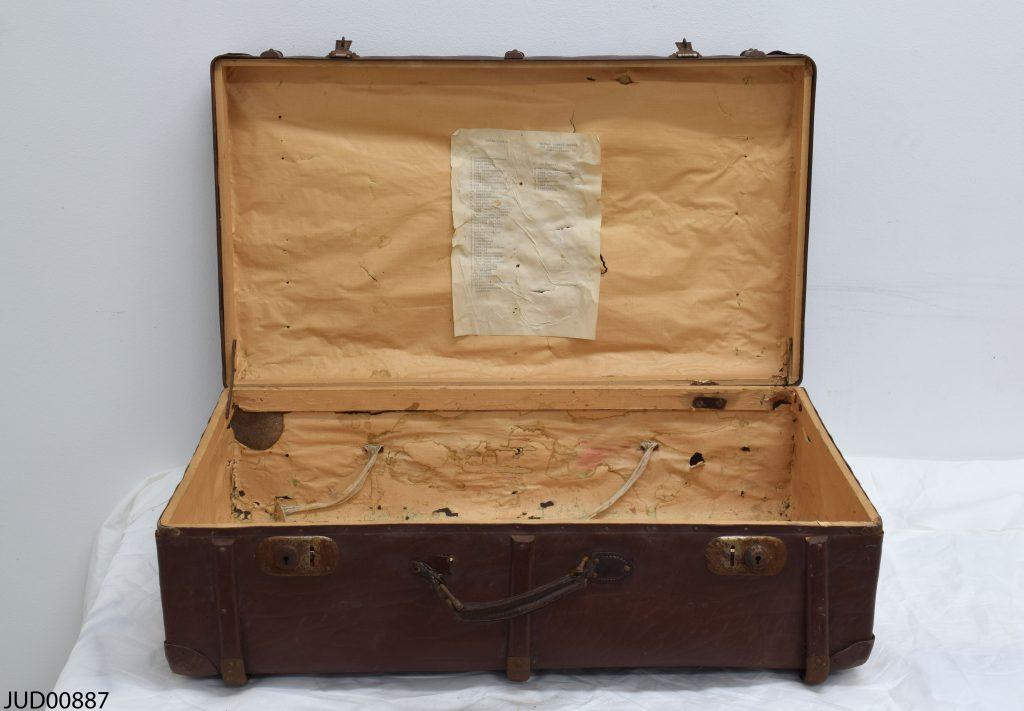 Foto av en brun resväska med en papperslapp klistrad på insidan av locket.