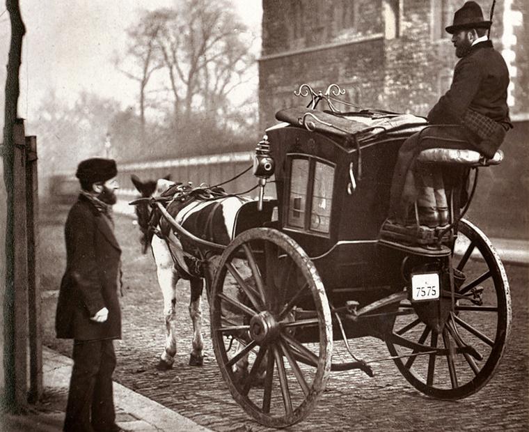 Svartvitt fotografi av hästtaxi med kusk i London. Kusken pratar med en man som står på trottoaren.