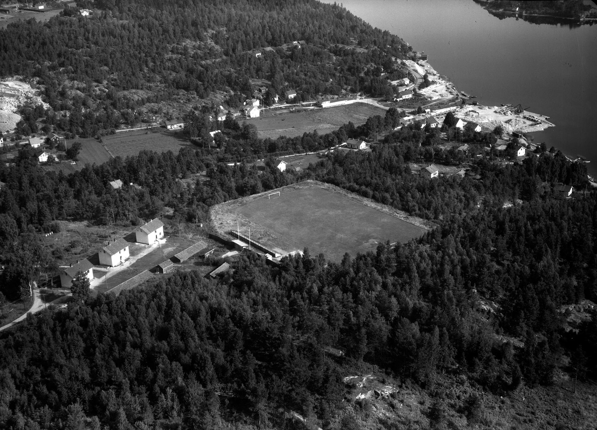 Flygbild av Krokstrand. Man ser mest skog och några vita hus. Havet syns i övre högra hörnet.