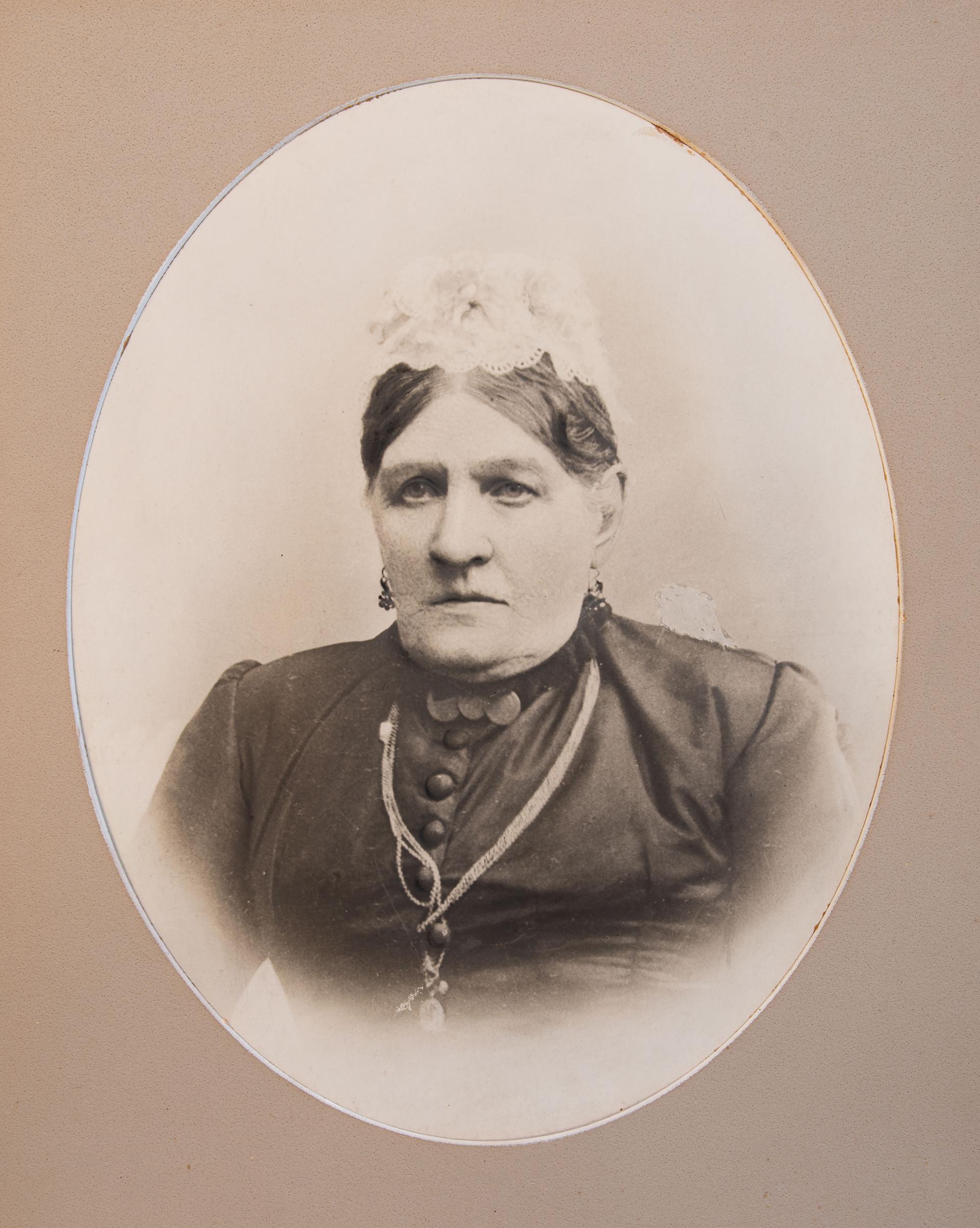Medelålders kvinna i mörk klänning och vit spetsmössa.