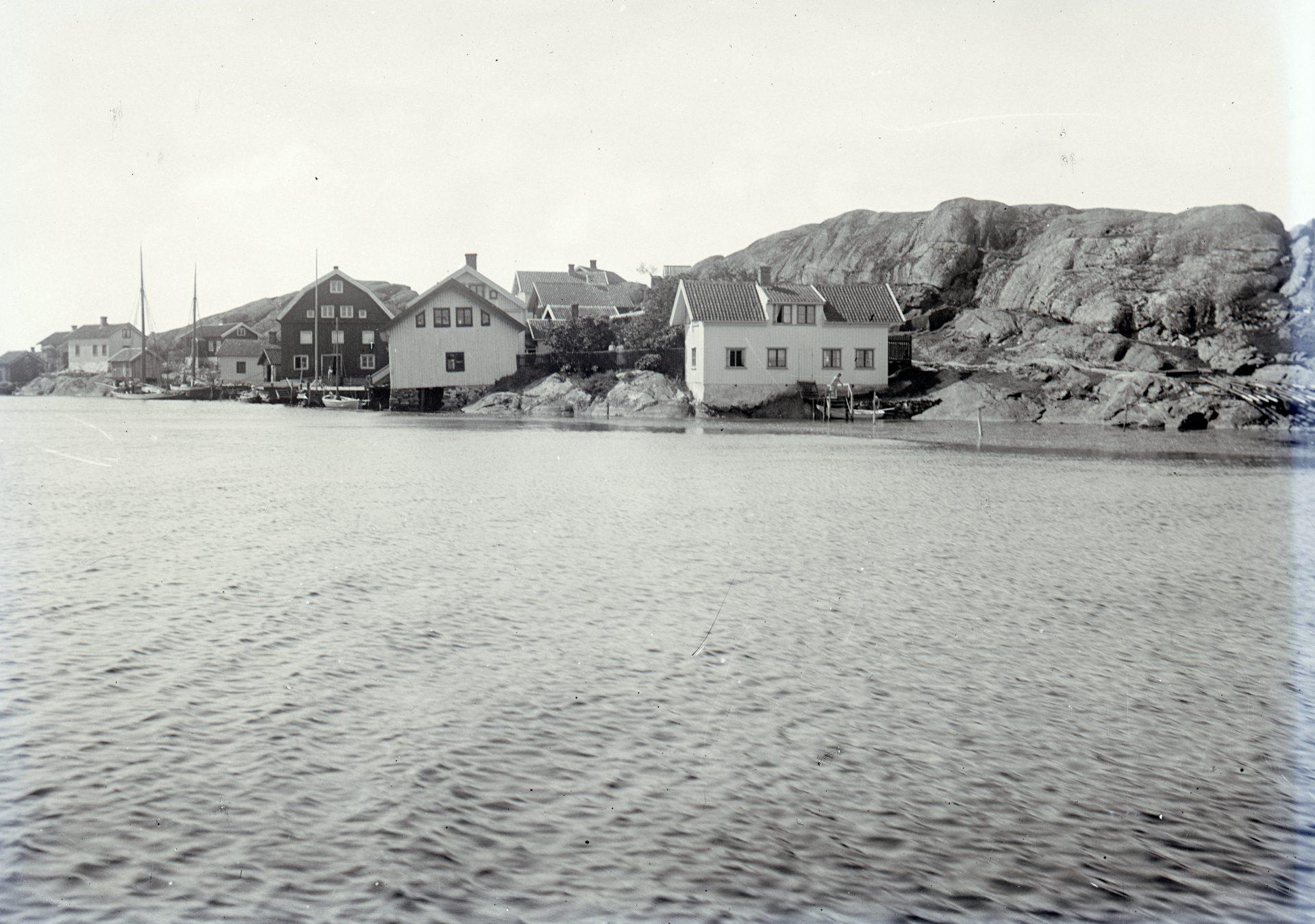 Svartvitt fotografi. I förgrunden vatten. I bakgrunden flera hus på en bergig ö.