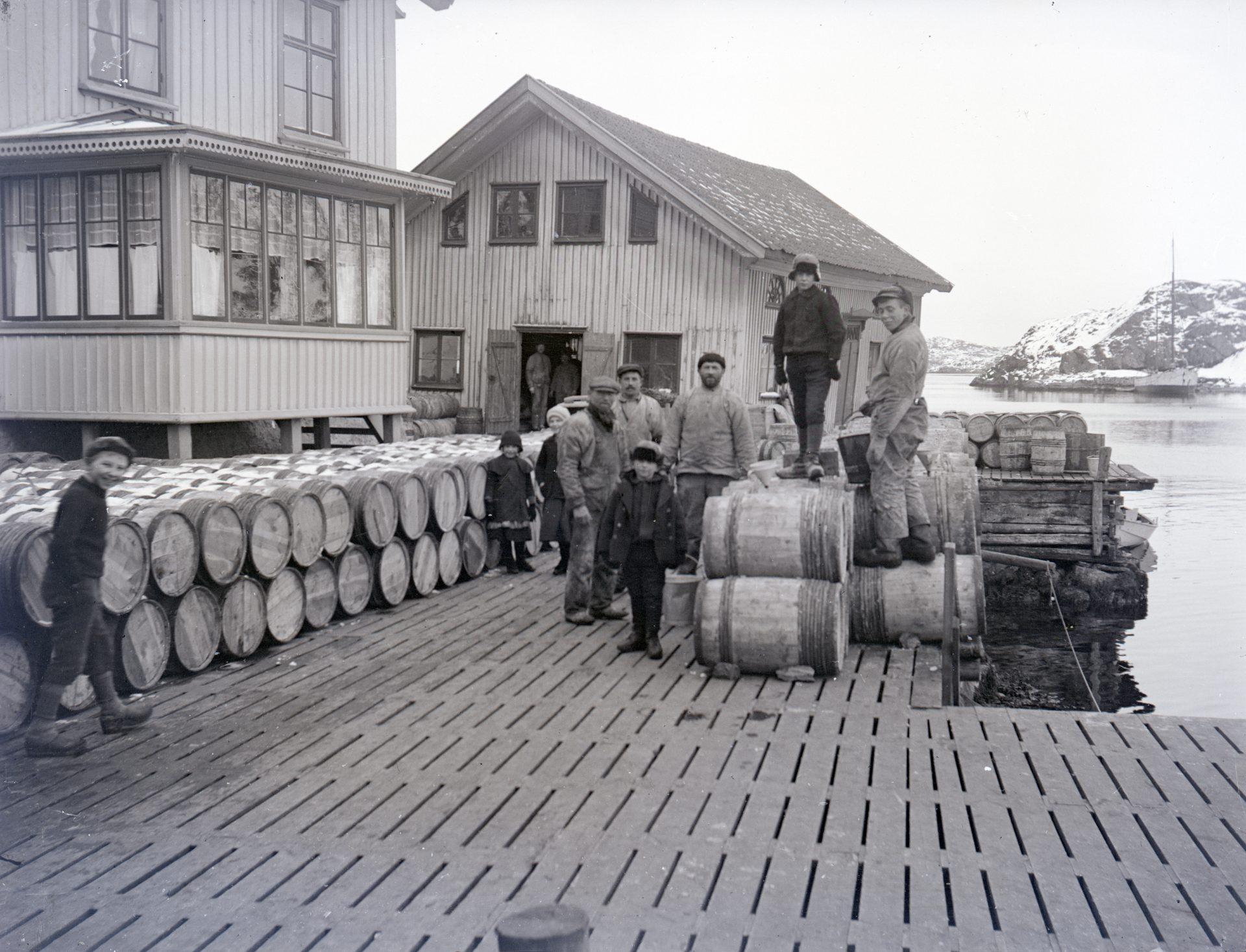 Svartvitt foto av män och pojkar på en brygga. På bryggan ligger tunnor och i bakgrunden syns två hus.