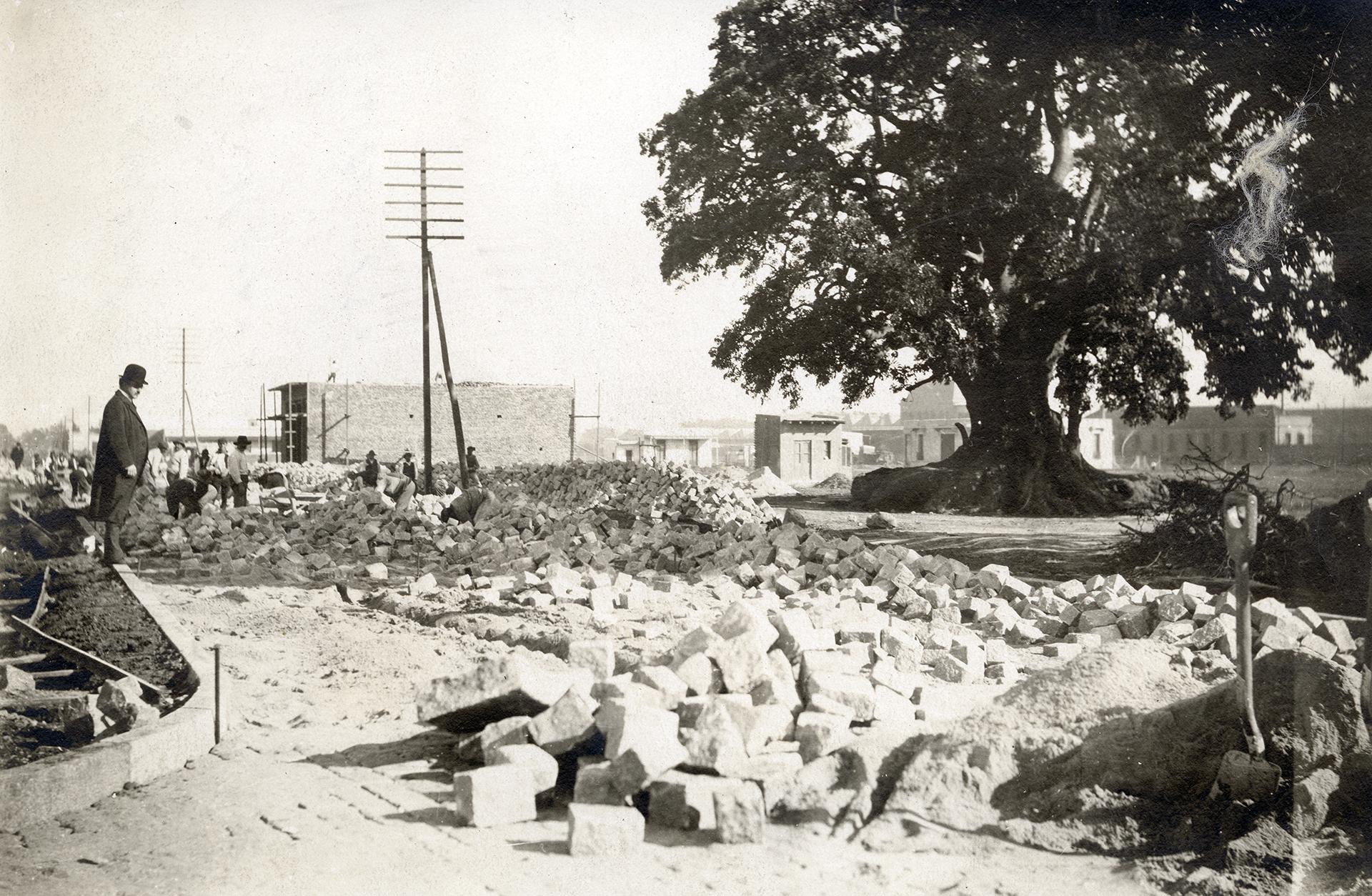 Bild av gatsten som ligger i högar på marken i Buenos Aires. En man i plommonstop tittar på stenhögarna.