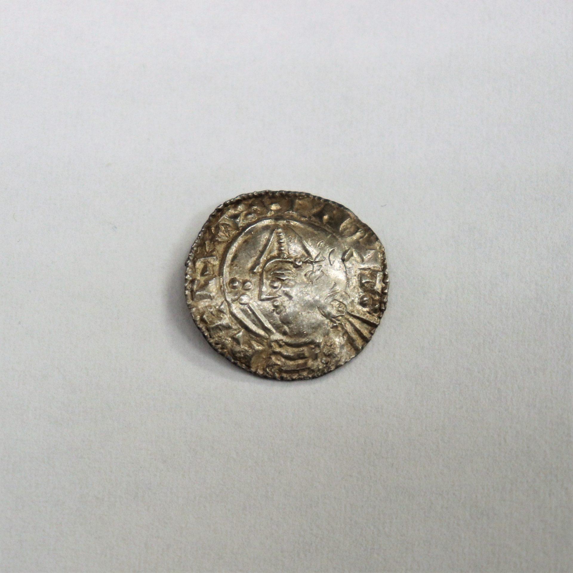 Silverfärgat mynt. I mitten ett ansikte med toppig hatt. Text runt kanten.