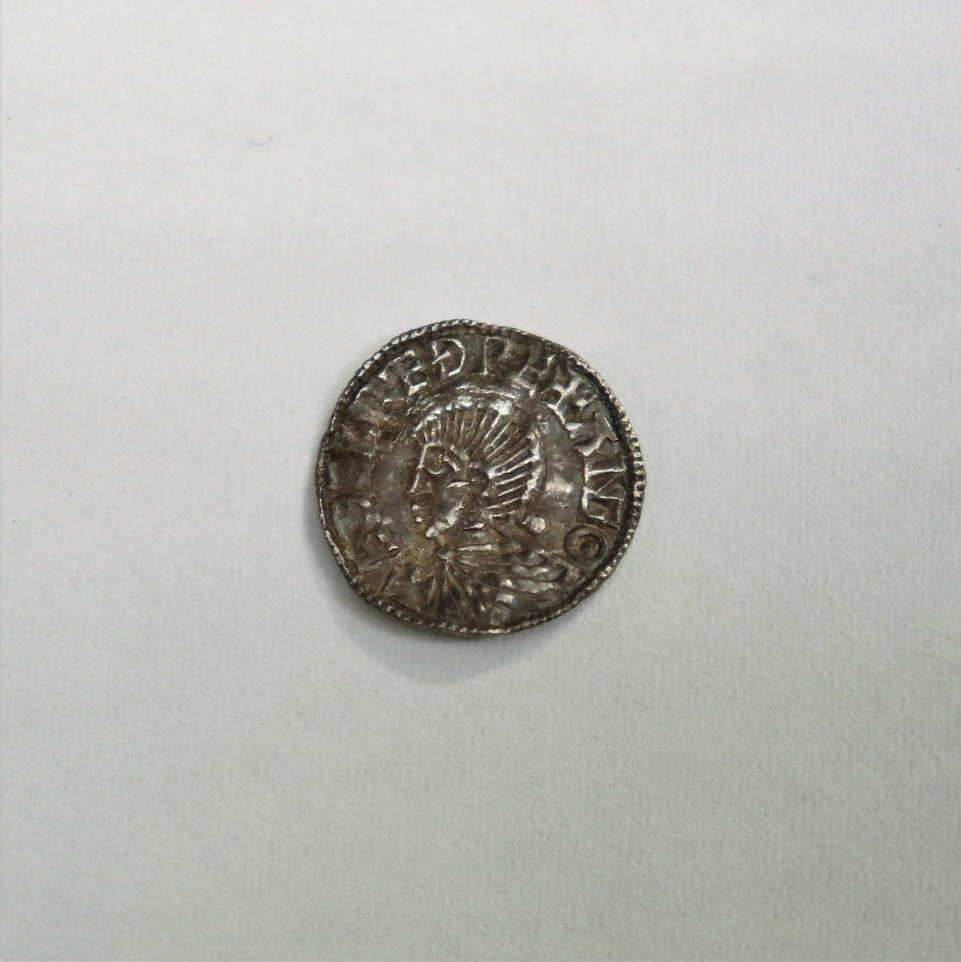 Silverfärgat mynt med ansikte i mitten och text runt kanten.