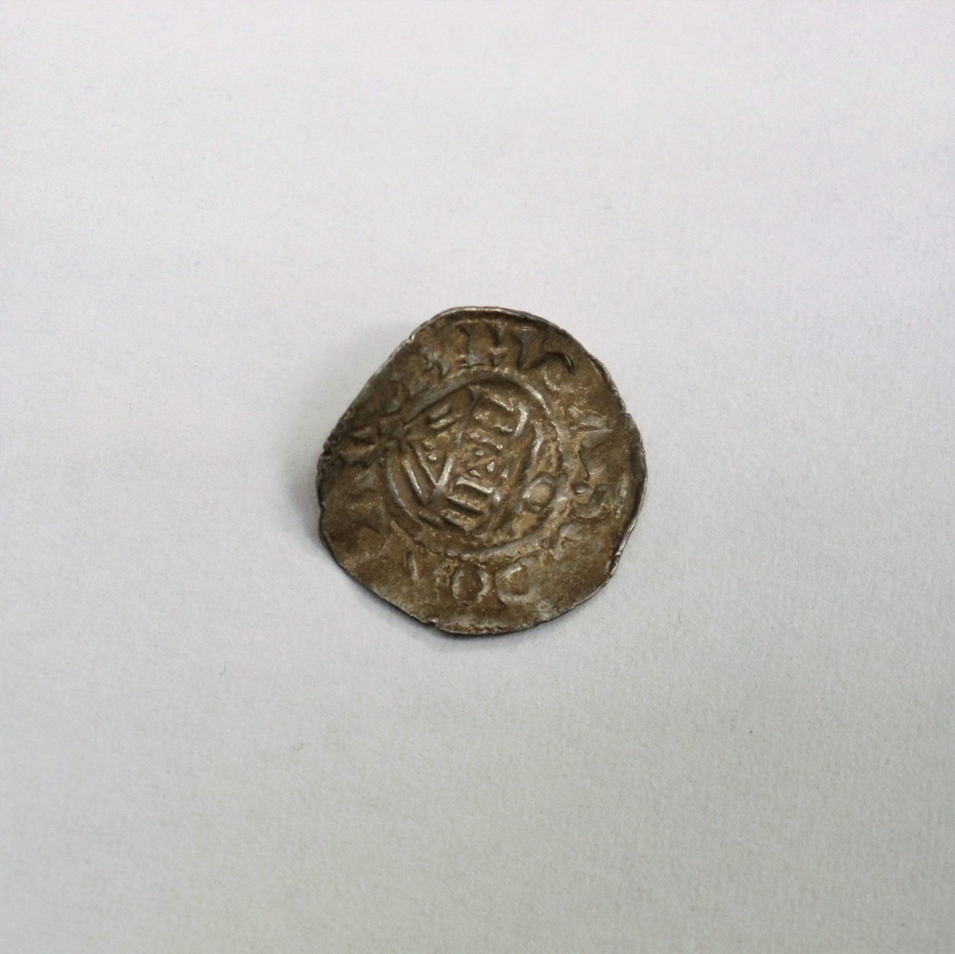 Buckligt mynt med missfärgningar.