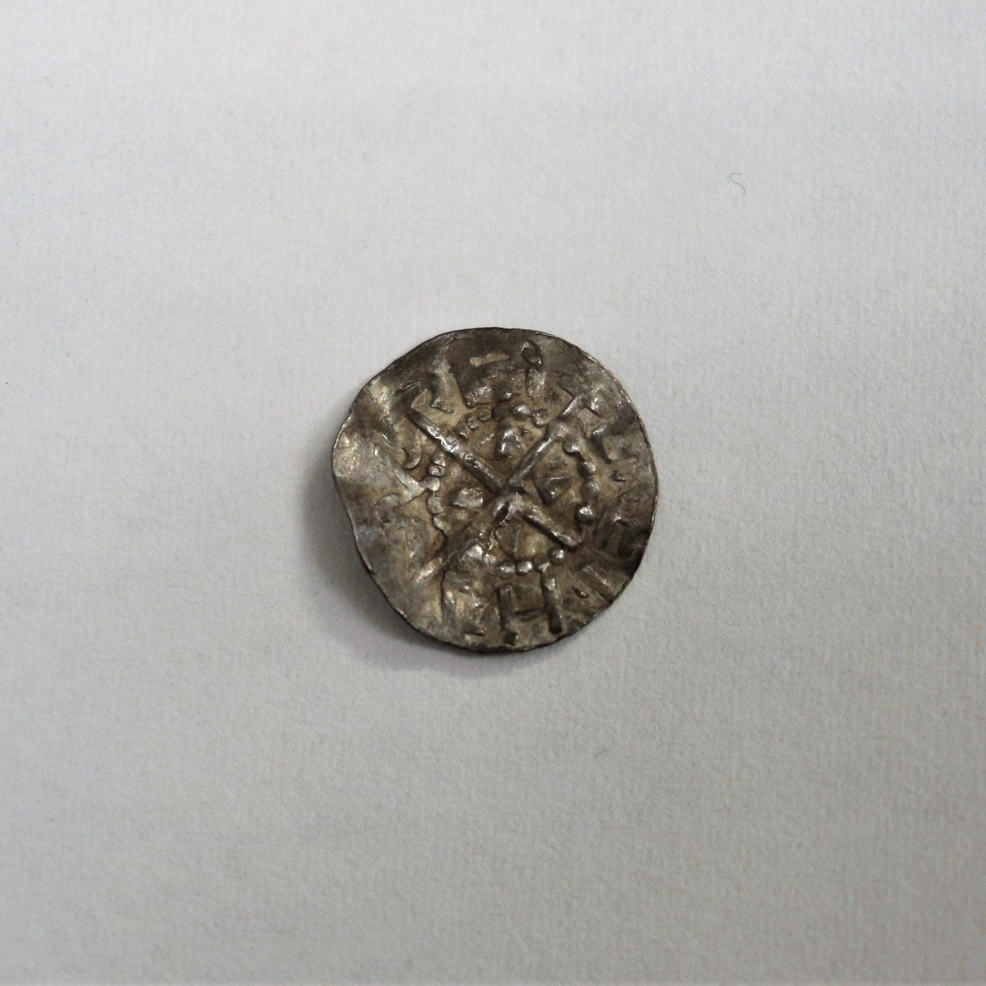 Buckligt mynt med kors i mitten och bokstäver runt kanten.