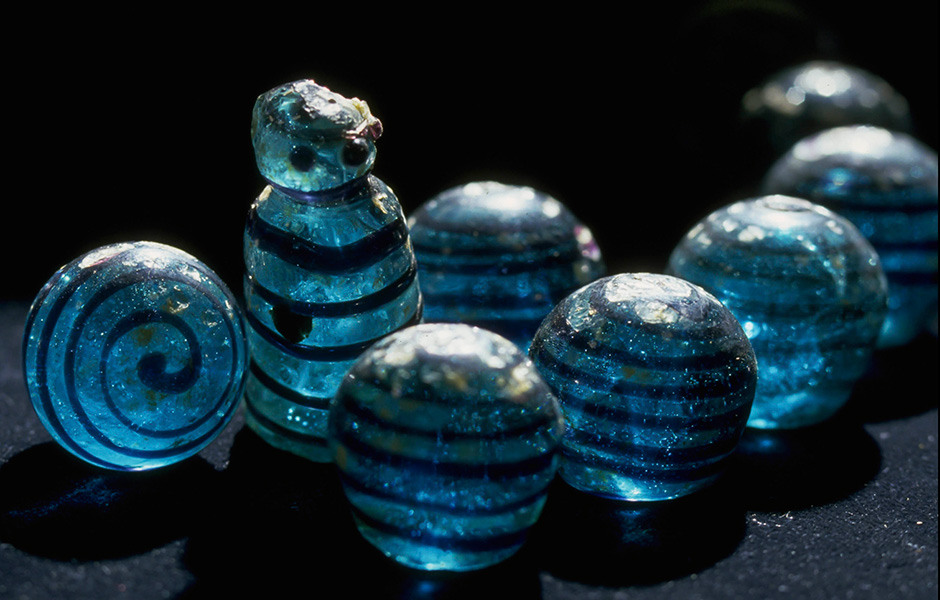 Foto av runda spelpjäser av turkost glas med svarta ränder. I mitten av bilden en högre spelpjäs