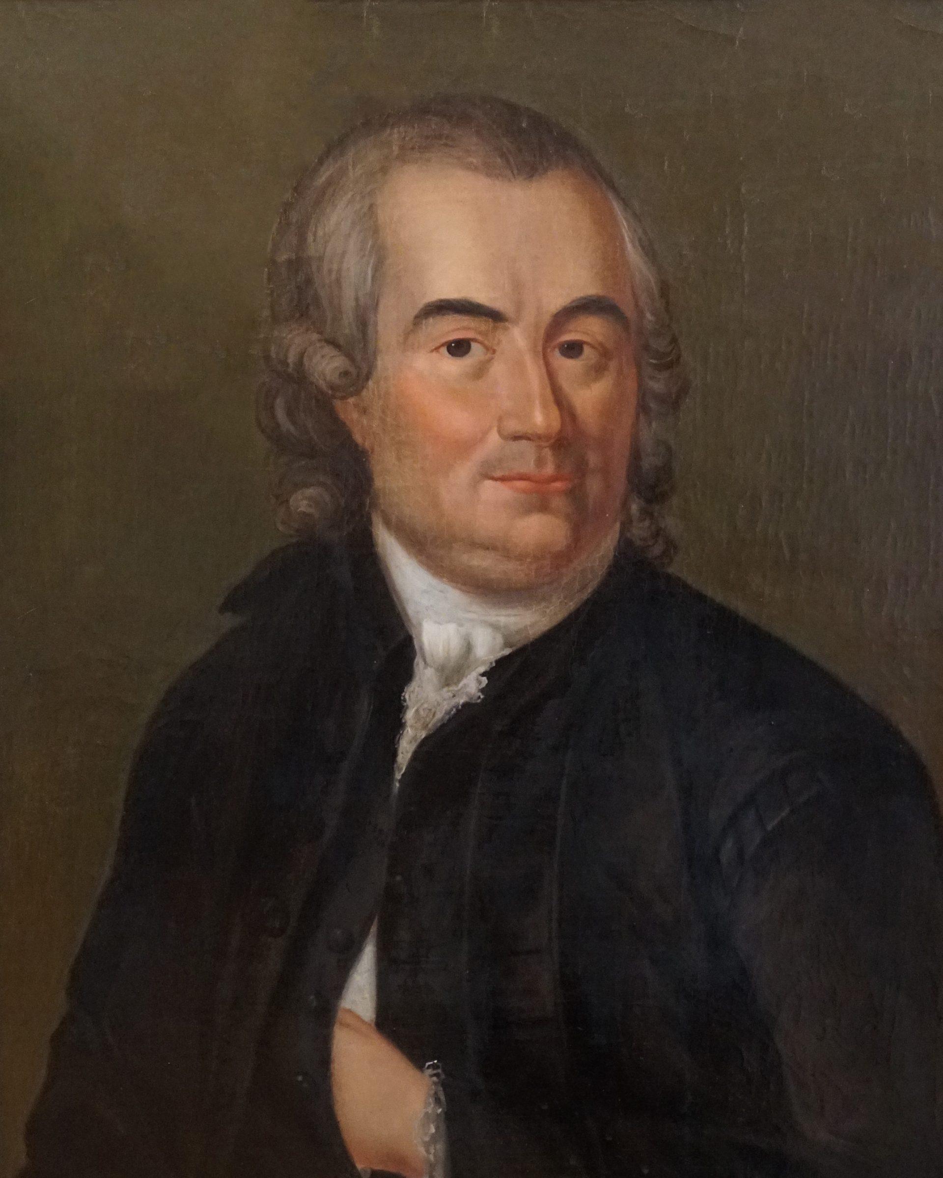 Porträtt av en man med grått hår och en svart rock.