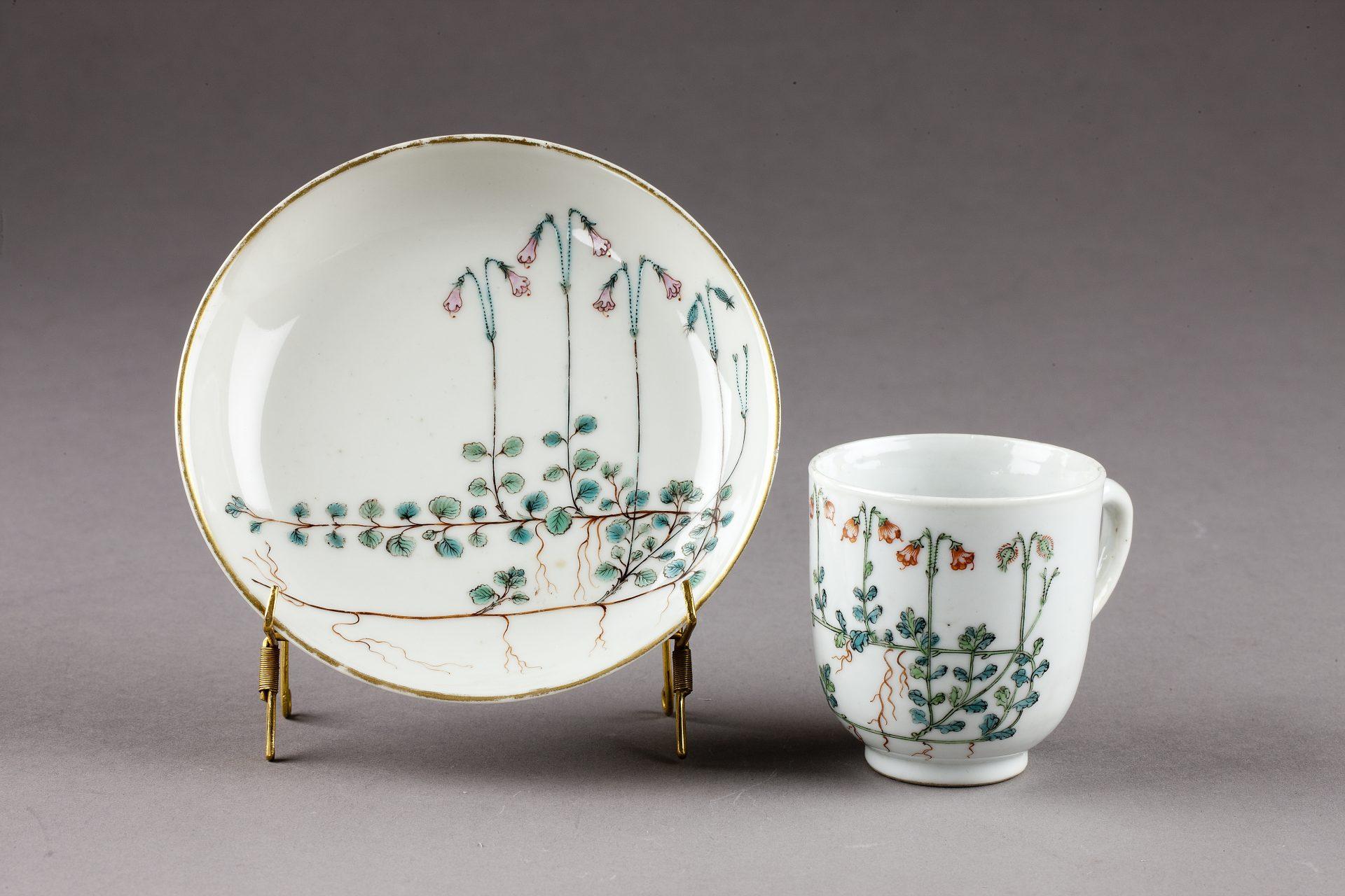 En kopp och ett fat av vitt porslin, dekorerade med rankor av linnéa.