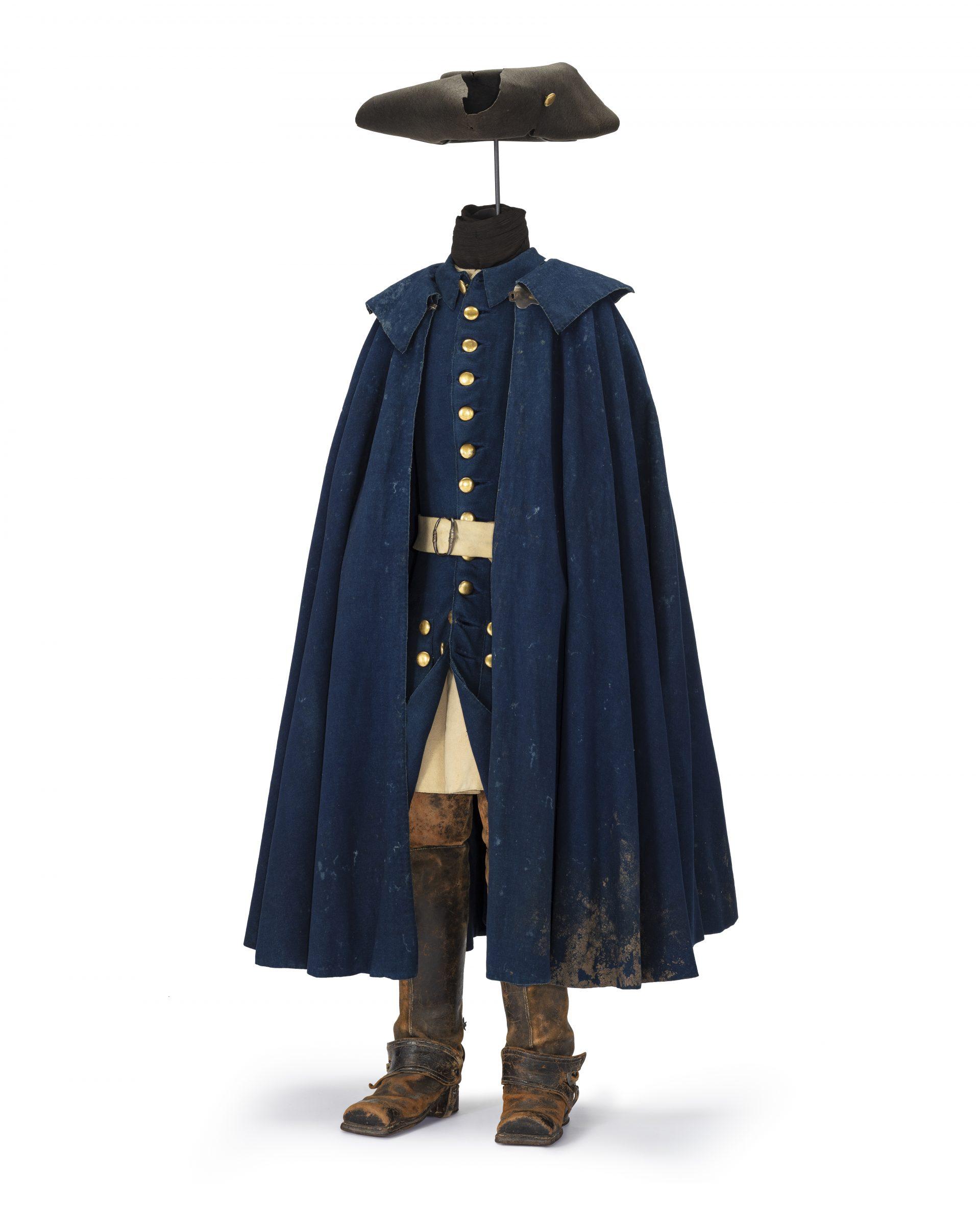 Uniform med blå rock med guldknappar, höga läderstövlar, en blå slängkappa och en trekantig, svart hatt.