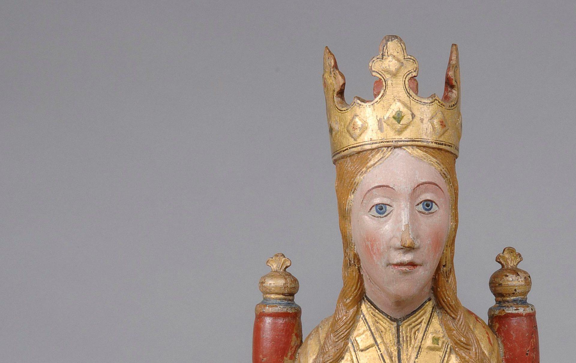Foto av bysten av en träskulptur som föreställer en madonna med guldkrona. Skulpturen är målad i guld och rött