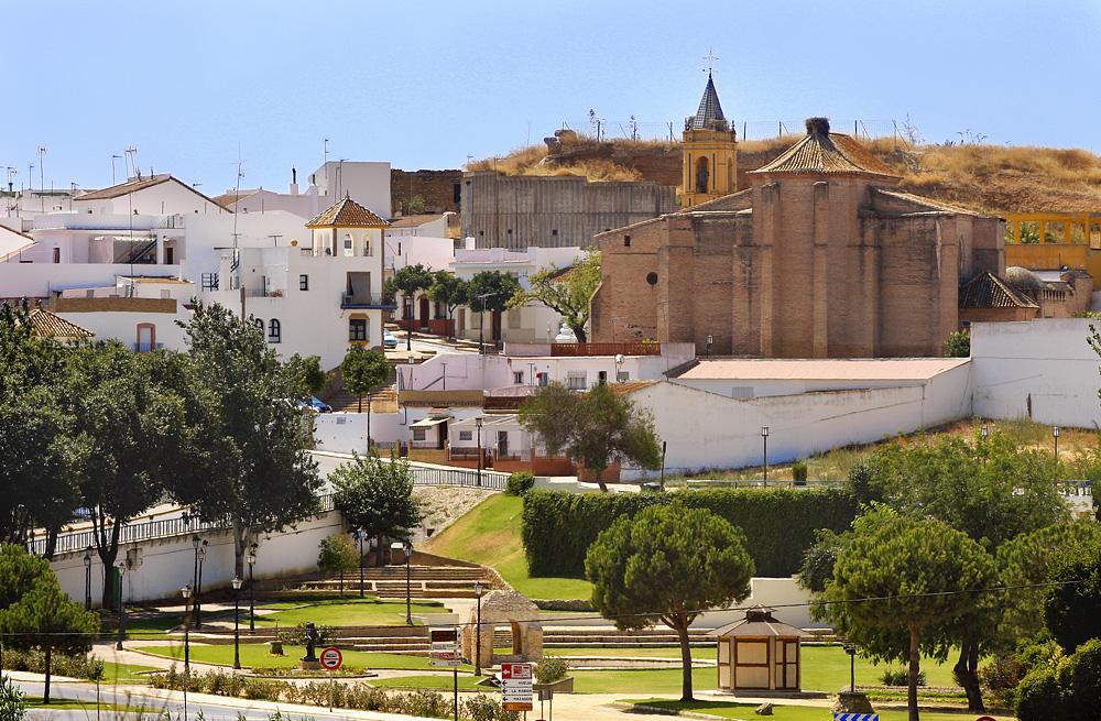 Vy över en liten stad med mest låga, vita byggnader. I mitten är en kyrka och i förgrunden en park med träd.