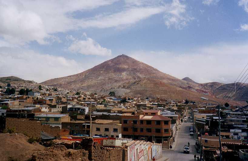 Vy över en stad med låga byggnader. I mitten är en gata med bilar. I bakgrunden syns ett spetsigt berg.