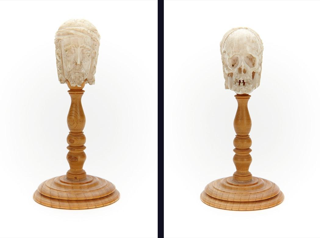 En liten snidad figur av ben på ett ställ av ljust trä.