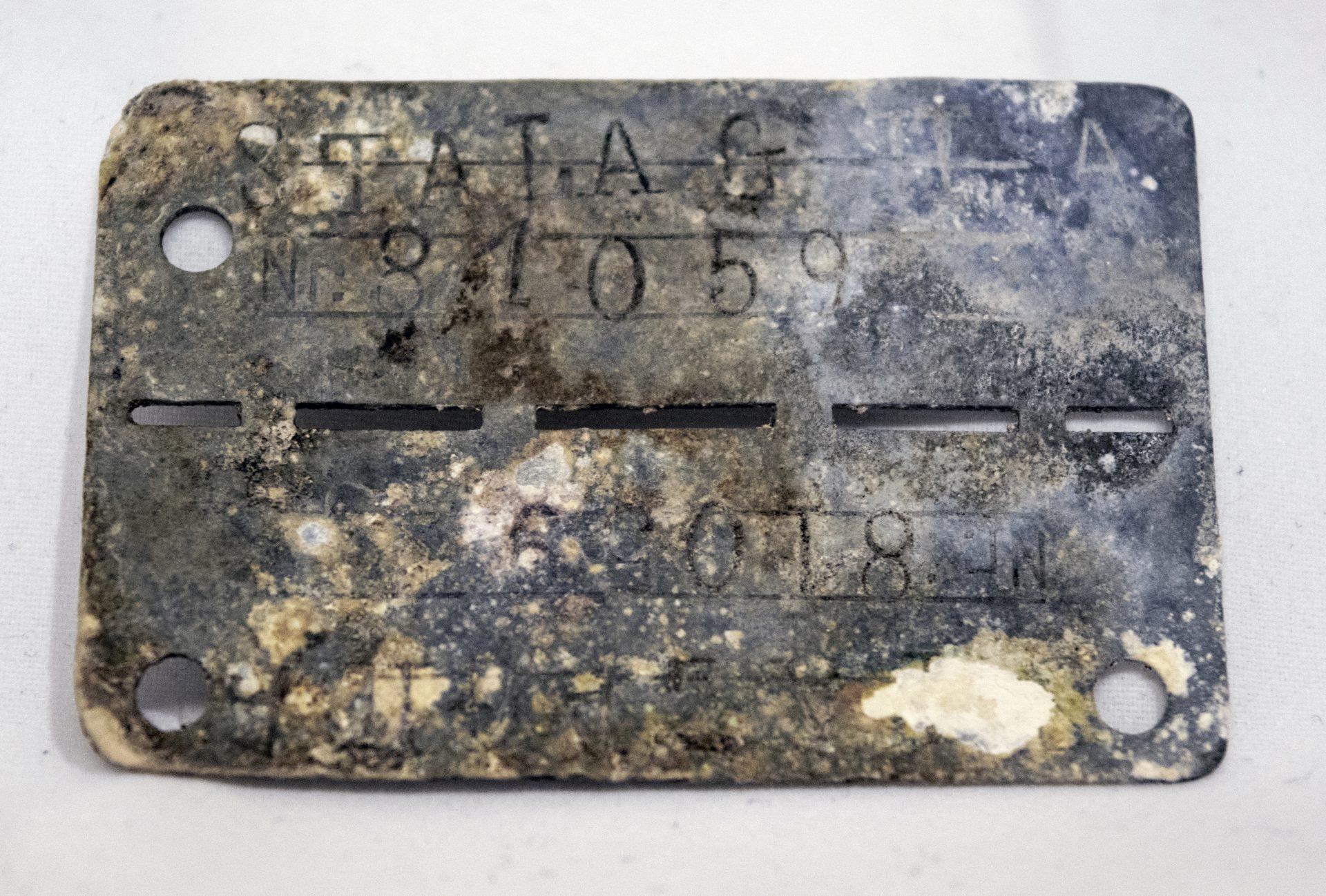 En ID-bricka av metall med runda och avlånga hål och instämplad text. Brickan är fläckig och sliten av ålder.