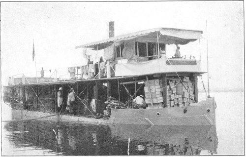 svartvitt foto av en flodbåt med mycket last i lådor. Flera personer finns ombord.