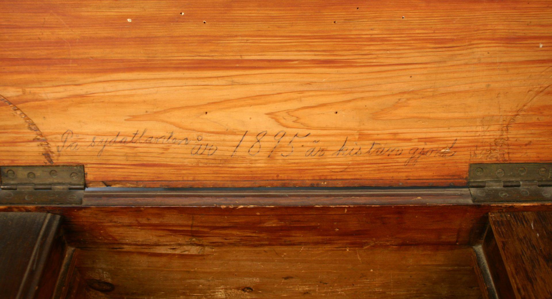 Detaljbild av en träkista med inskription om ägaren.