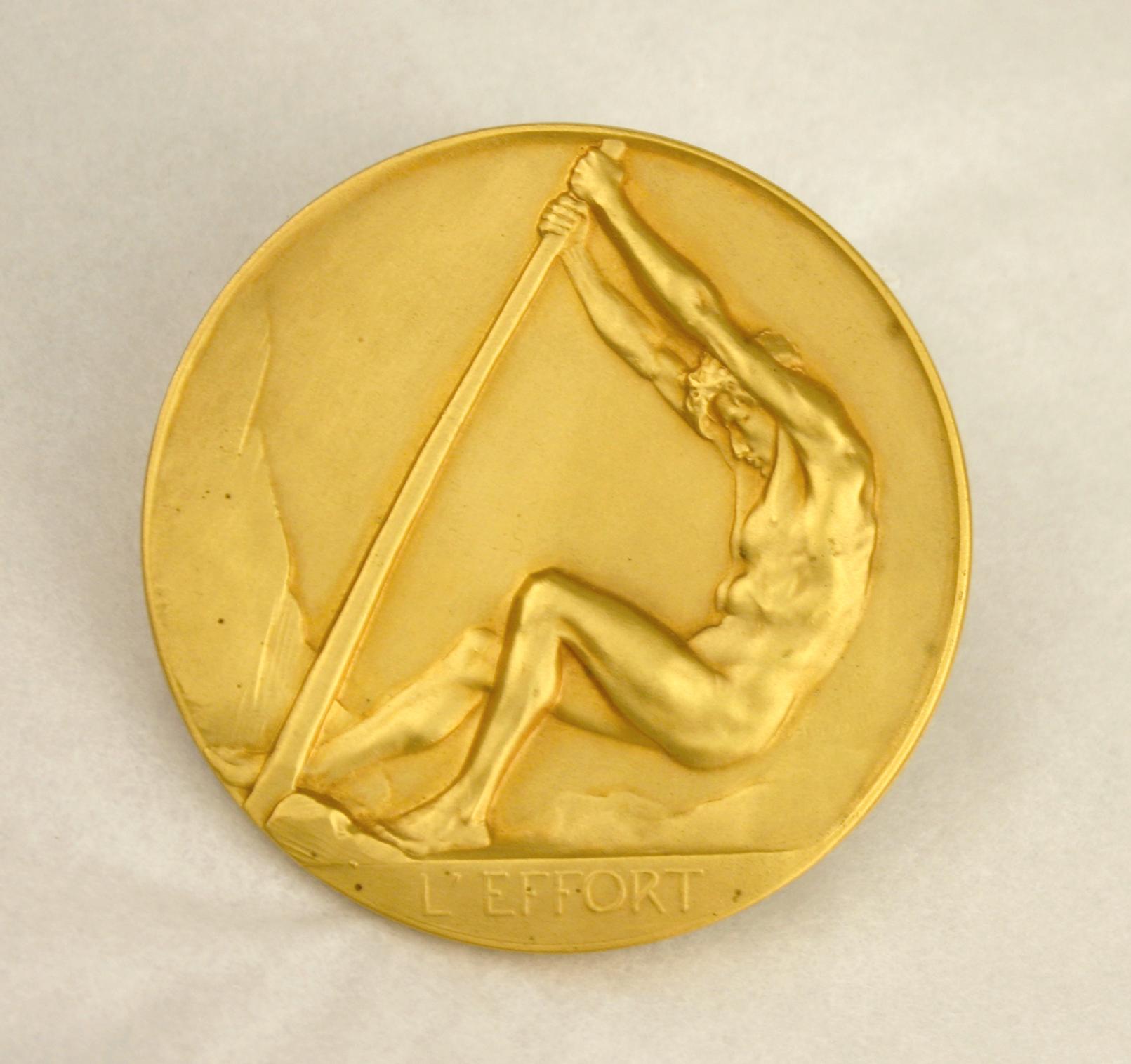 """Guldmedalj med en naken man som bänder med en hävstång. Under honom finns texten """"l'effort""""."""