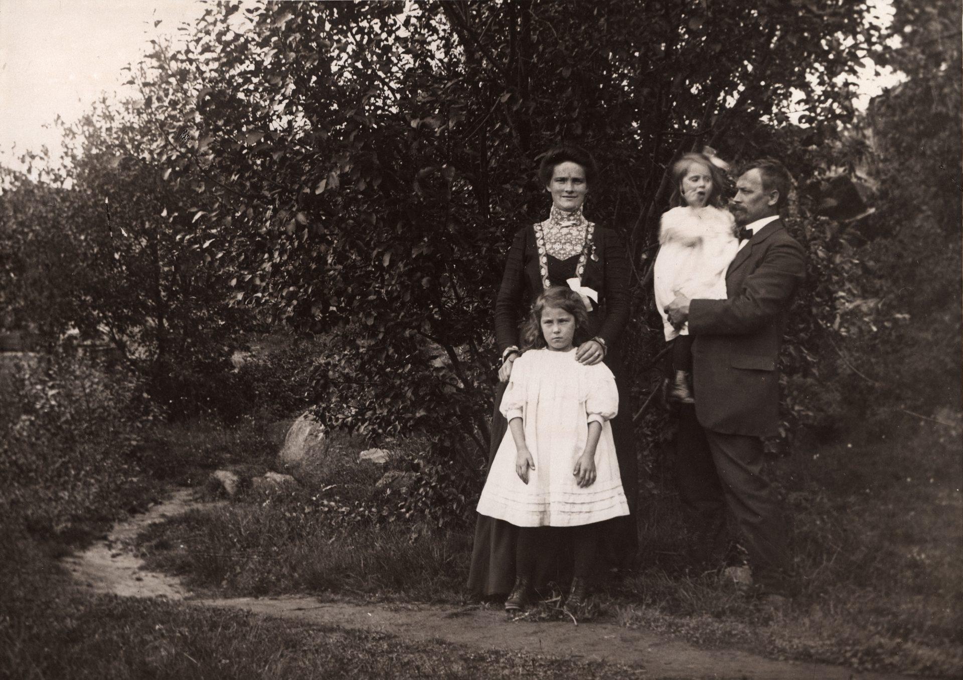 Svartvitt foto. En kvinna, en man och två små barn står framför en träddunge. Framför dem går en liten stig.
