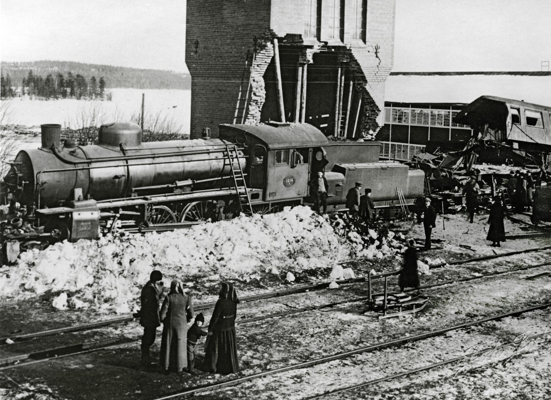 Ett tåg som har spårat ut. Vagnarna ligger på sidan. Flera människor står och tittar på.