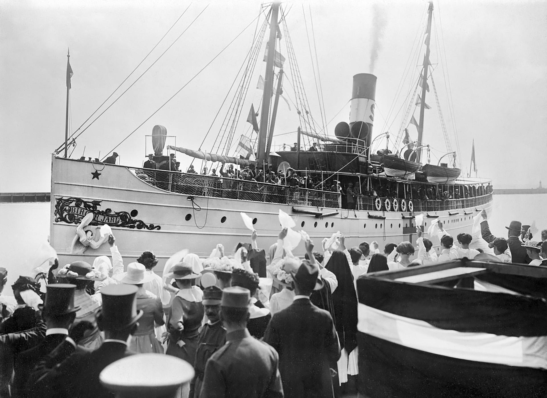 Fartyget Birger Jarl. Människor på kajen vinkar med vita näsdukar till människorna ombord.