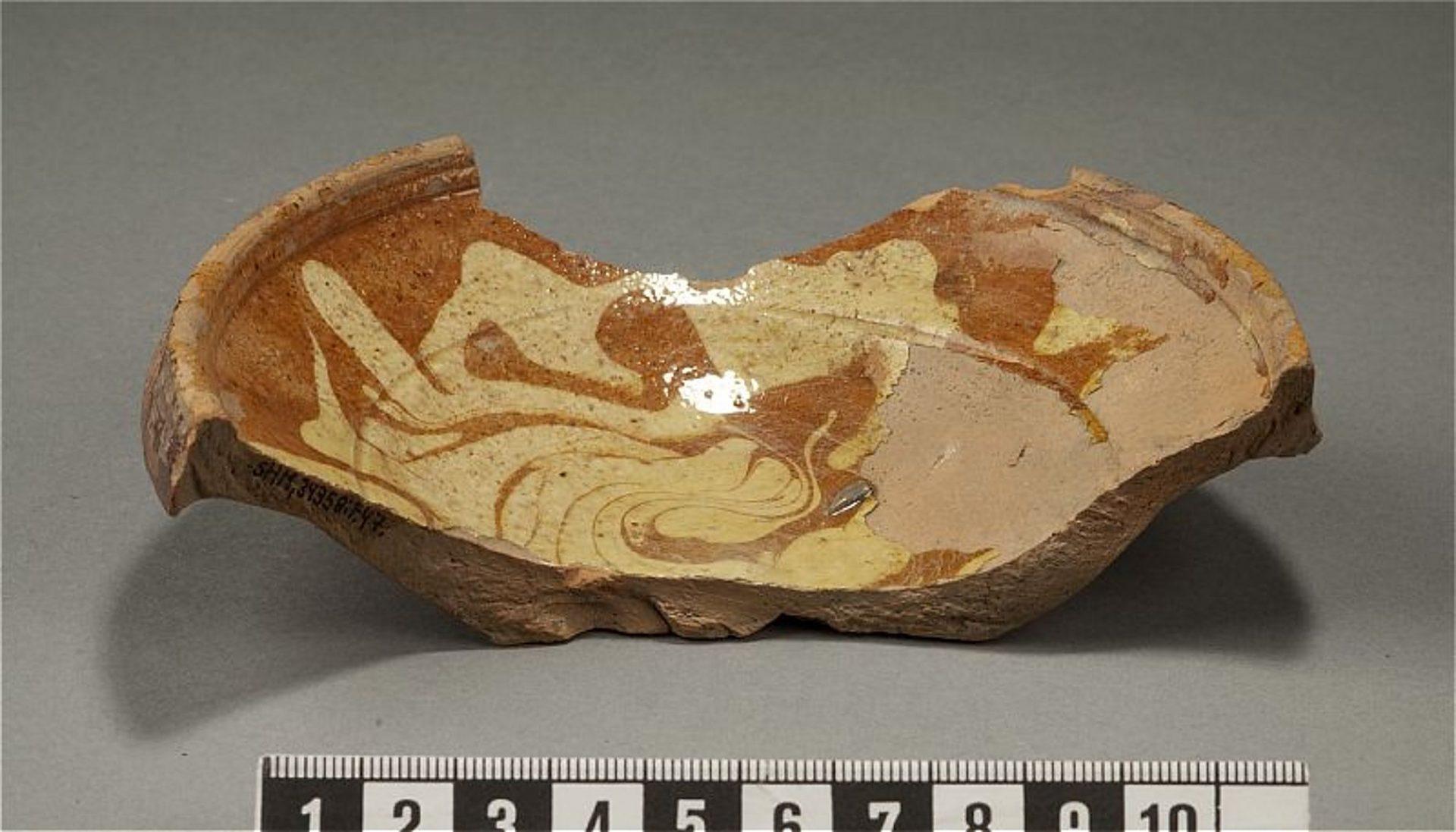 Skärvan av en keramikskål är ldekorerad i rödbrunt och vitt och glaserad. Skålen är vid och har en tjockare kant.