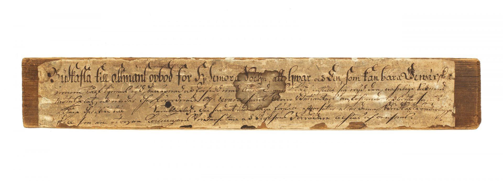 Ett trästycke med ett påklistrat papper med text.