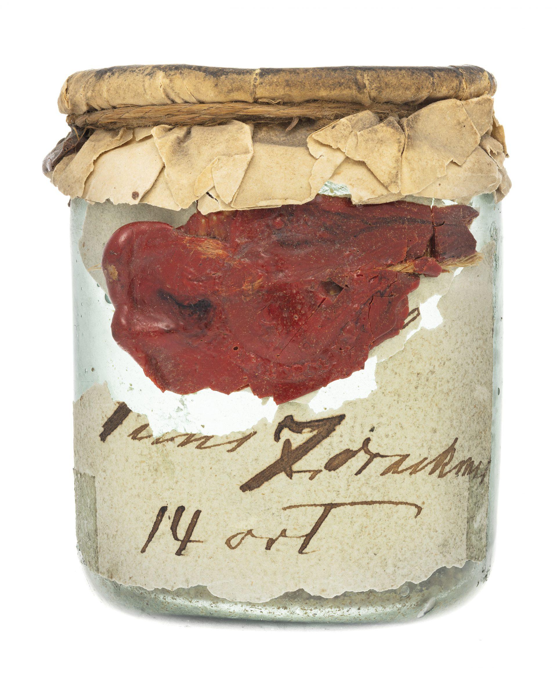 En glasburk med brunt papper som lock och ett rött sigill.