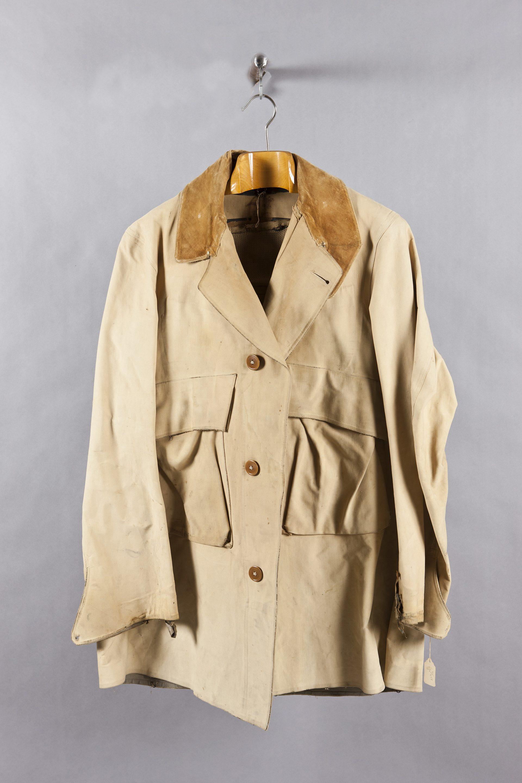 Jacka av beige tyg och mellanbrun krage. Jackan hänger på en galge.