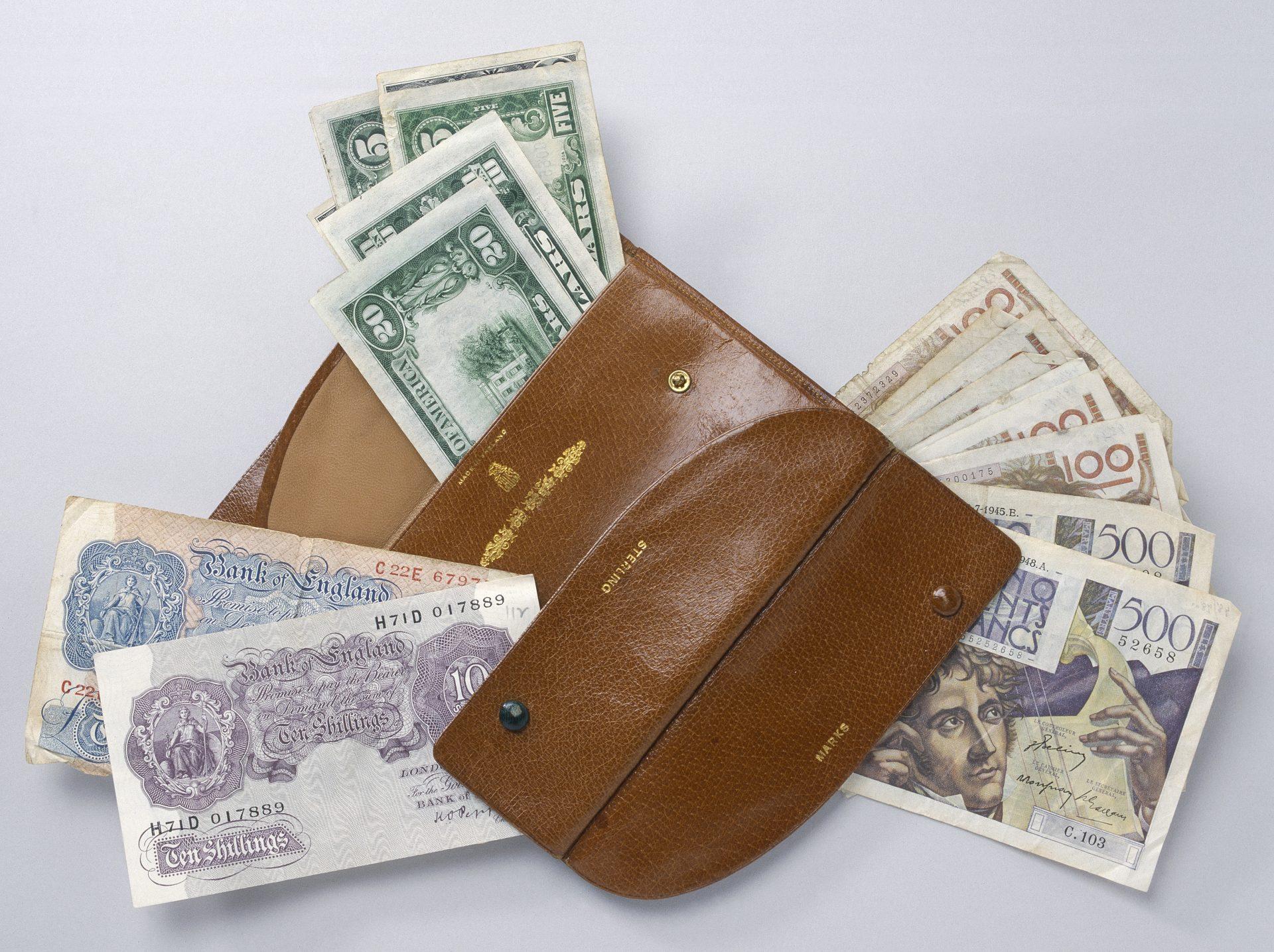 Engelska banksedlar som ligger i en skinnfärgad plånbok