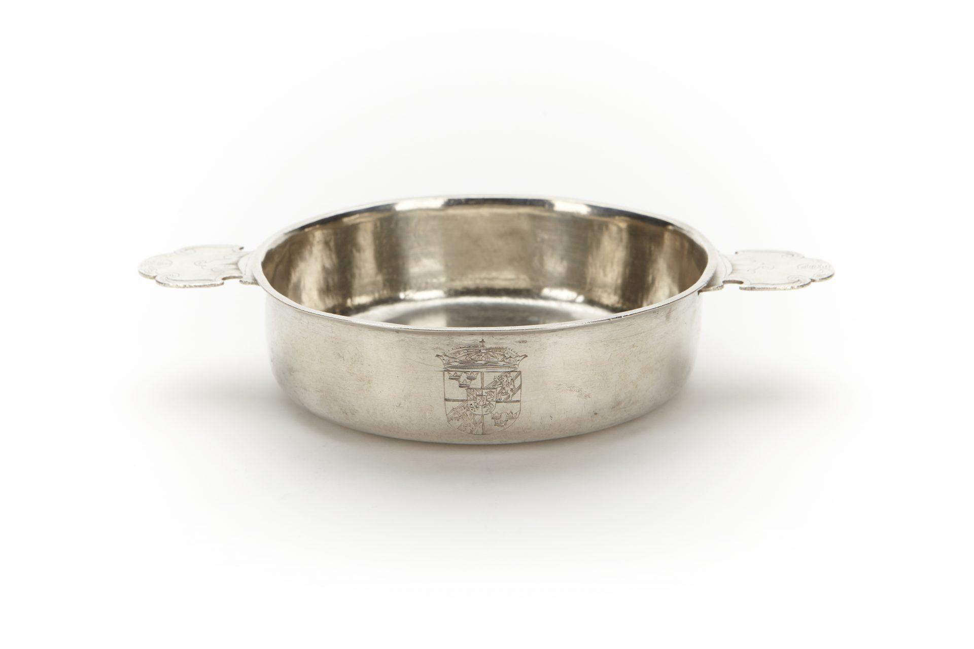 En silverskål med två handtag.