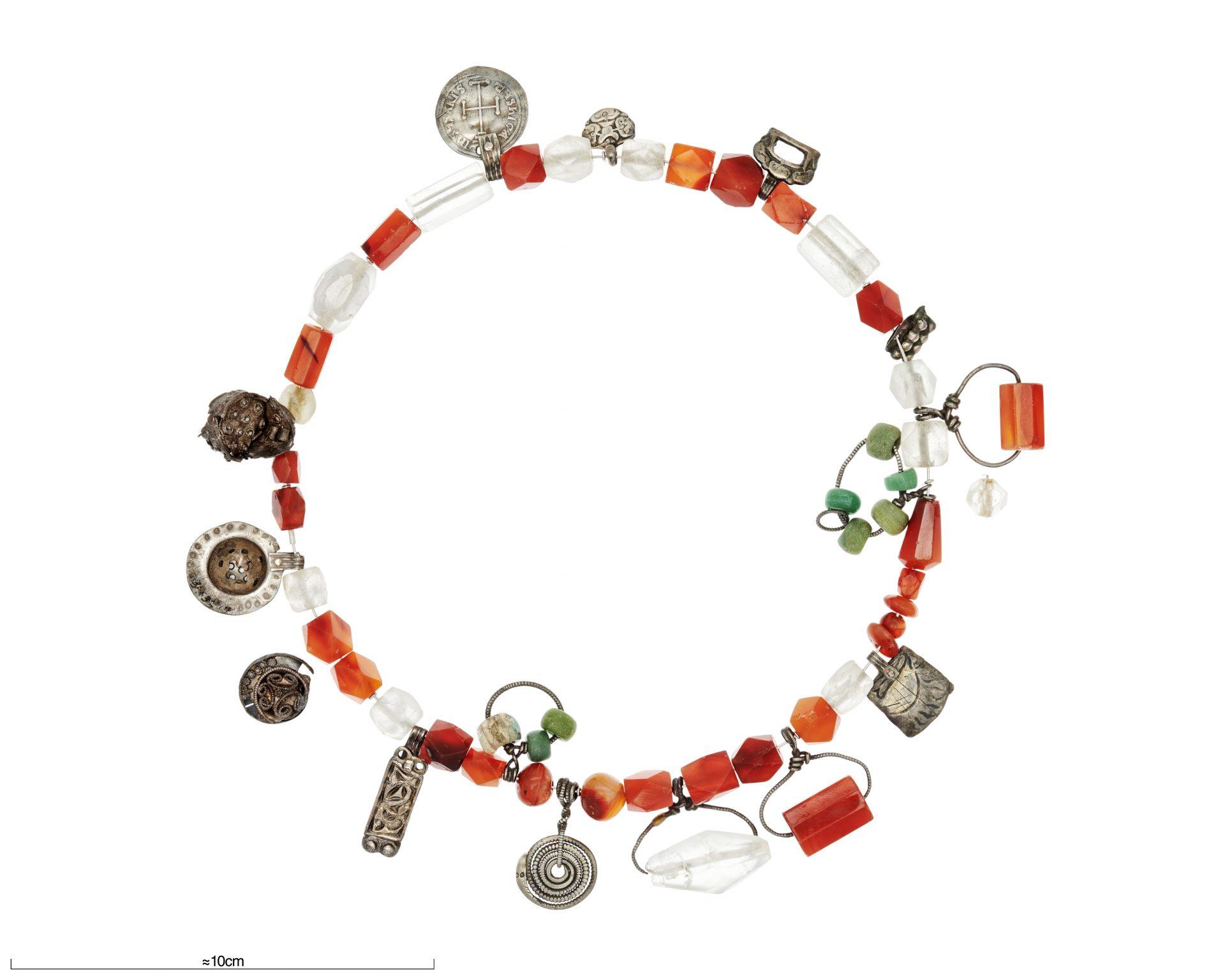 Ett halsband med glaspärlor och hängen av metall.