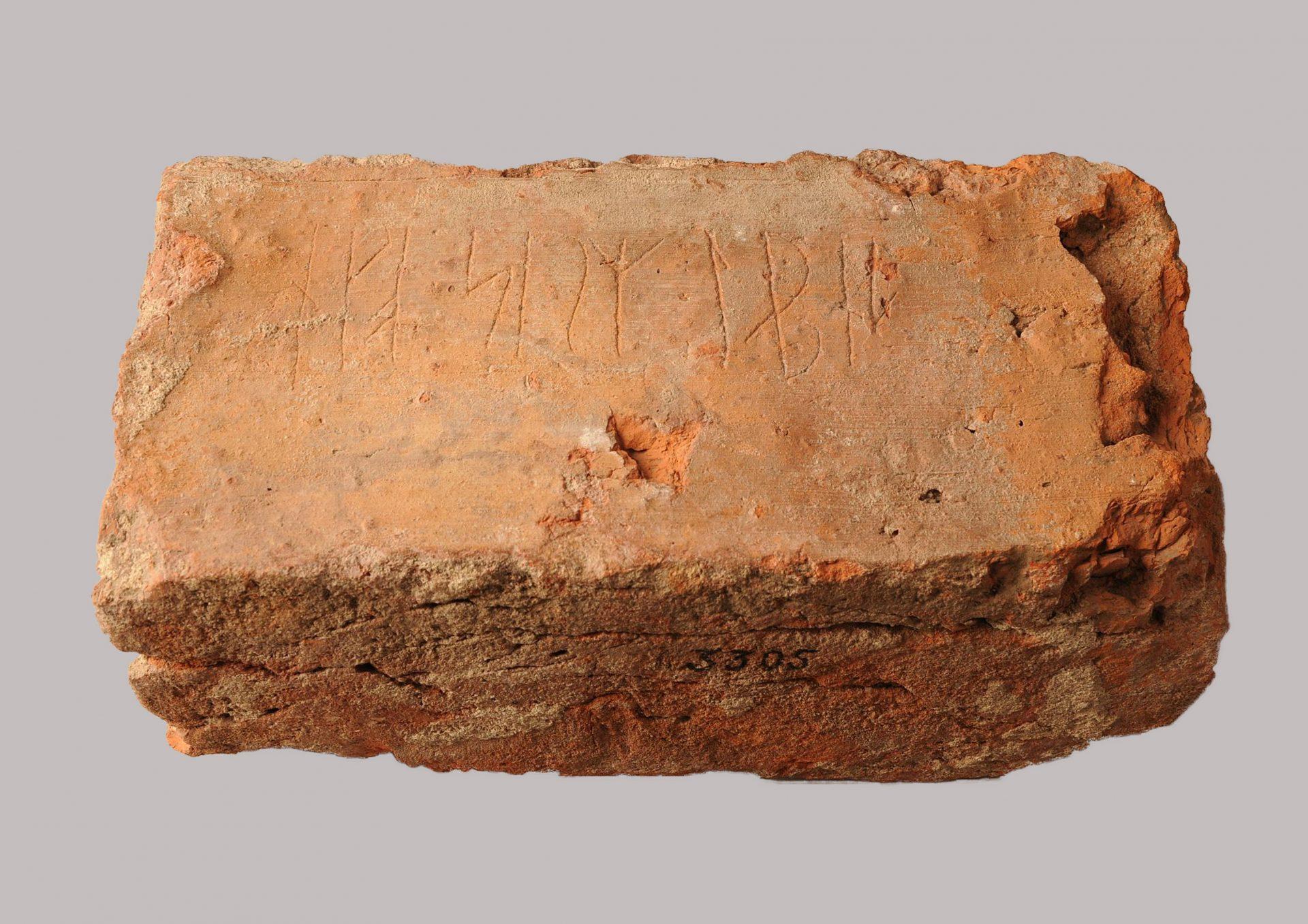 """En tegelsten med inristade runor som läser """"ego sum lapis""""."""