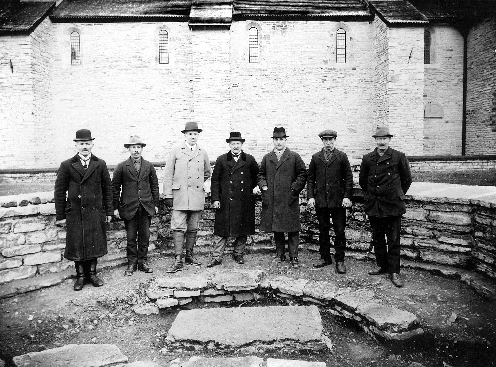 Sju män står framför en låg mur. Fotot är taget på 1920-talet.