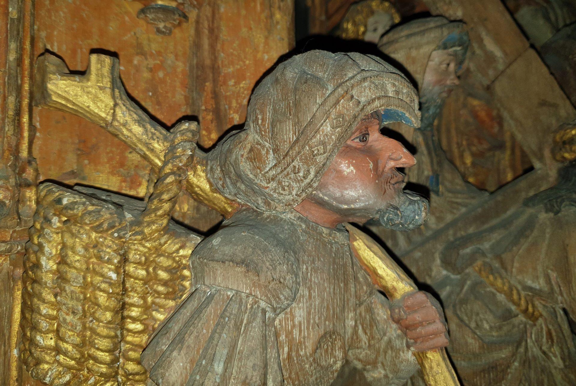 Träskulptur föreställande en man med en korg på ryggen. Från ett medeltida altare.