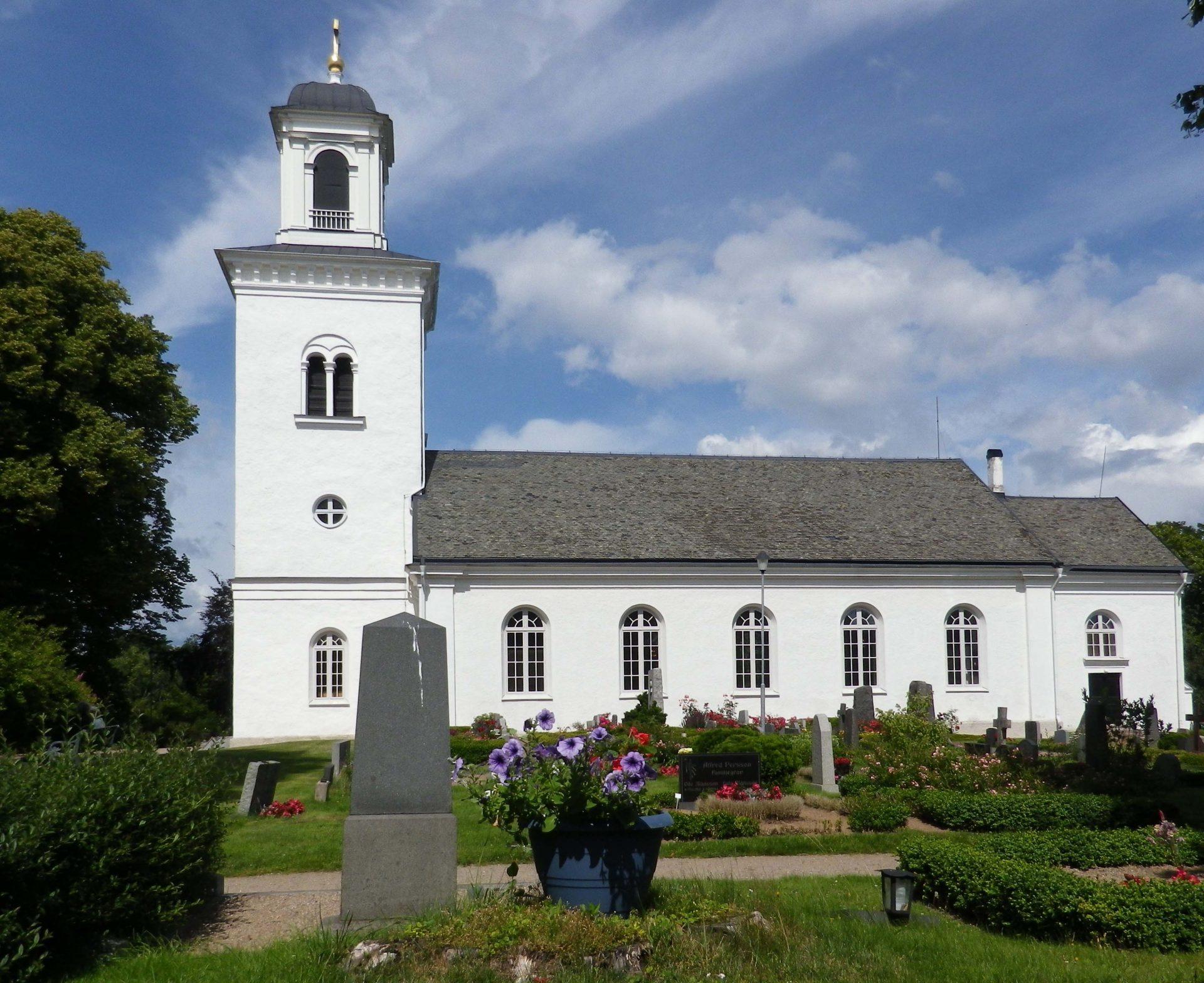 En vitmålad kyrka med högt torn.