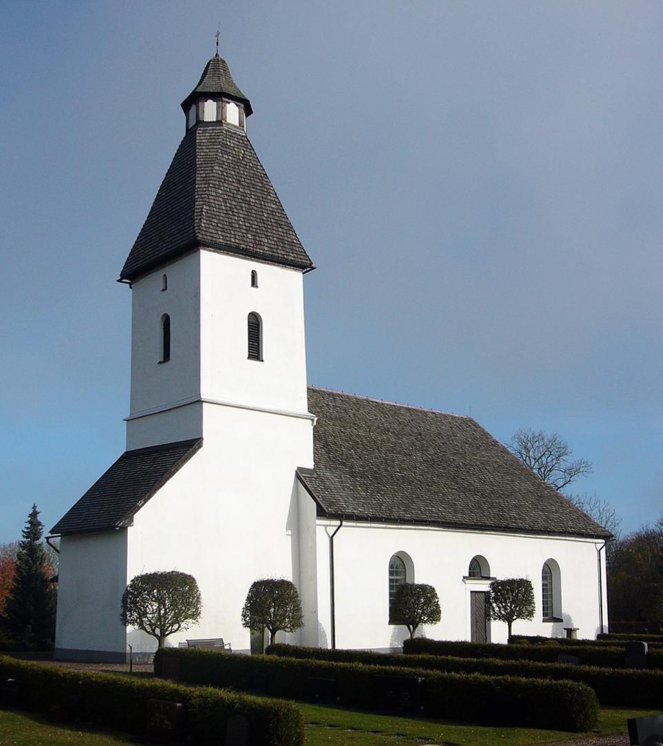 En vit kyrka med svart tak. Framför kyrkan står några träd. Himlen är molnfri.