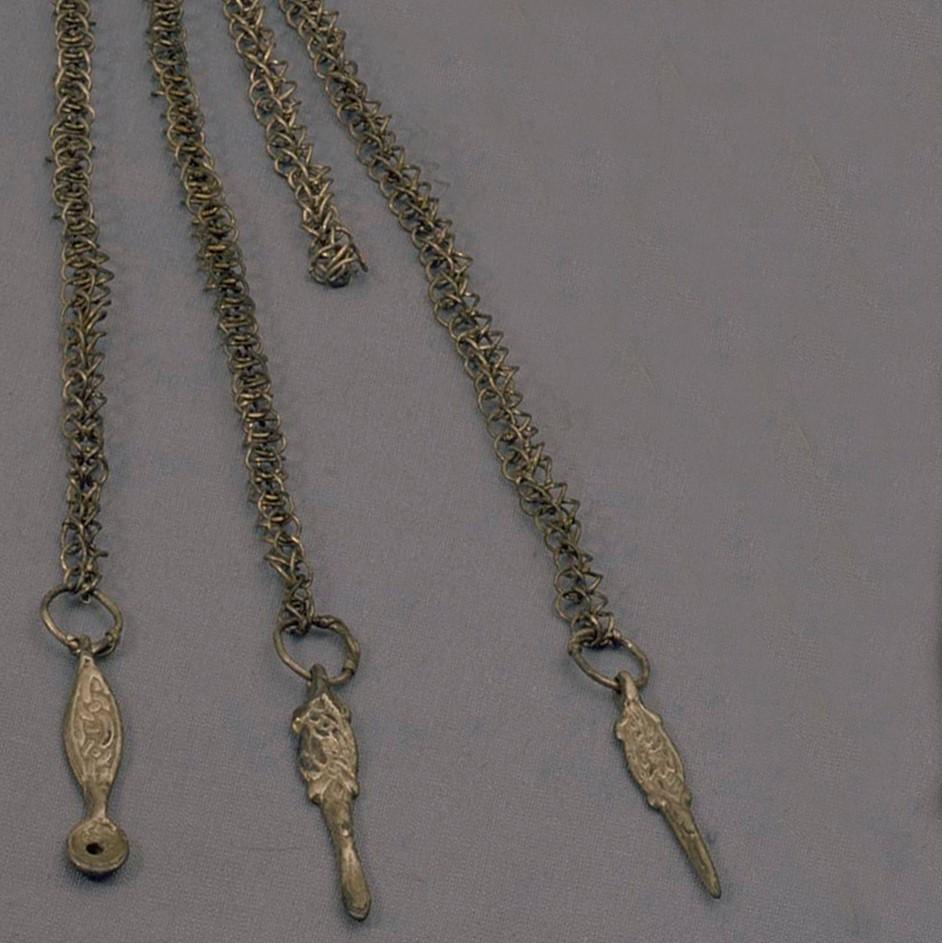 Detalj av ett dräkthänge i silver. Tre små prydnader hänger från kedjor.