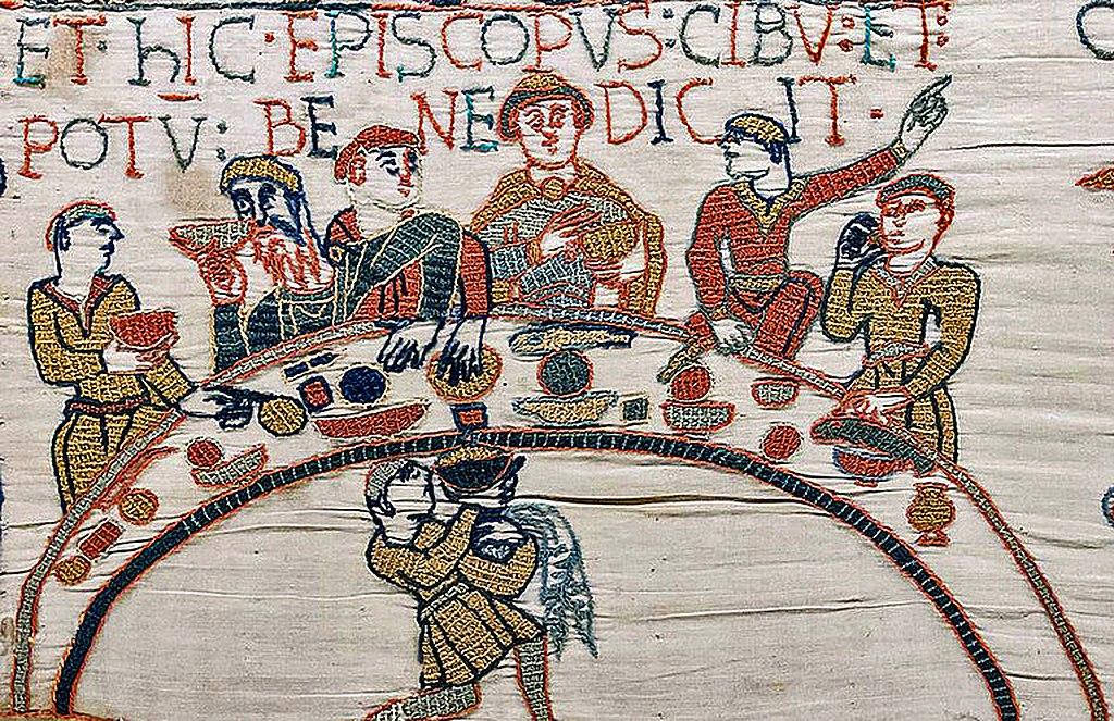 Detalj ur Bayeuxtapeten som visar ett sällskap vid sittande bord.