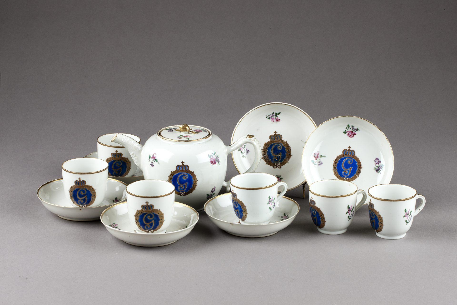 Servis med sex koppar, fat och en tekanna i vitt porslin med dekor i blått och guld.
