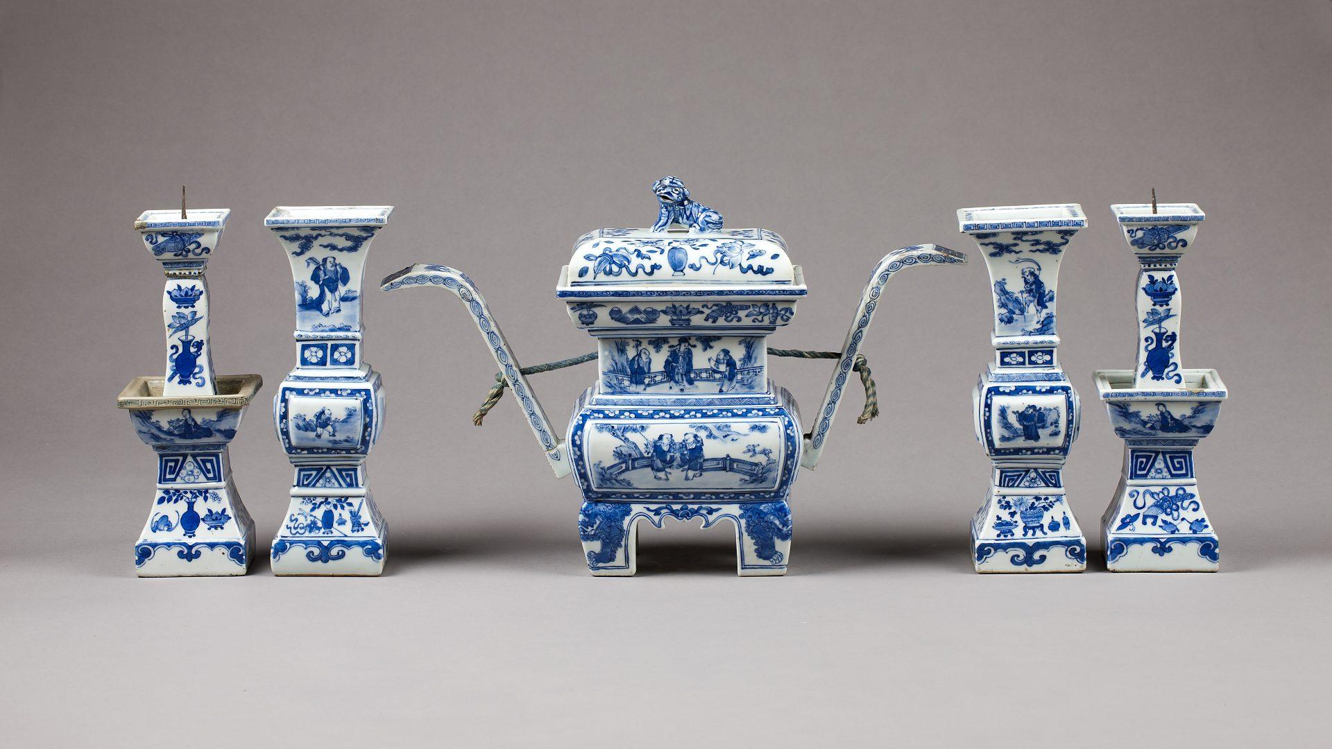 Kinesiska porslinsföremål av vitt porslin med blå dekor. På bilden finns två vaser, två ljussstakar och ett rökelsekar.