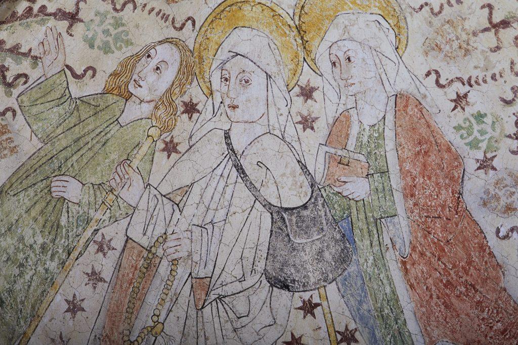 Målning av tre personer som är klädda i pilgrimsdräkter. Personen i mitten bär på en väska och en pilgrimsstav.